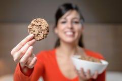 Hongerige vrouw met koekje bij nacht stock afbeelding