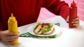 Hongerige vrouwelijke holdingsketchup en mosterd, hotdogworst op lijst, smaakstof stock afbeelding