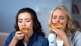 Hongerige vrouwelijke vrienden die van heerlijke pizza, Italiaanse keuken, voedsellevering genieten stock fotografie