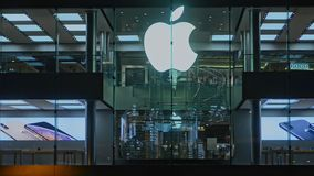 Hongkong, China - August 2019: Symbol of Apple famous brand on store building and reflection of people in city.