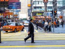 HONGKONG CHINY, Grudzień, - 9 2016: Biznesowego mężczyzny odprowadzenie przez crosswalk na drodze z miasta tłem hong kong zdjęcia royalty free
