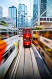 HONGKONG KINA - APRIL 29, 2014: Två-berättelse spårvagnar på gatorna av staden i rörelse Hög trafik och hastighet royaltyfri bild
