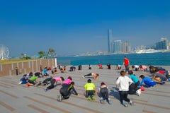 HONGKONG KINA - JANUARI 26, 2017: Folkmassa av folk som gör Tai Chi Exercising i morgonen, med en downton av staden Arkivfoton