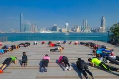 HONGKONG KINA - JANUARI 26, 2017: Folkmassa av folk som gör Tai Chi Exercising i morgonen, med en downton av staden av Hong K Royaltyfri Foto