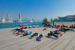 HONGKONG KINA - JANUARI 26, 2017: Folkmassa av folk som gör Tai Chi Exercising i morgonen, med en downton av staden av Hong K Arkivbilder
