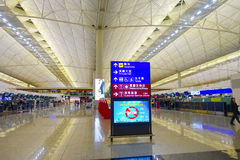 HONGKONG KINA - JANUARI 26, 2017: Oidentifierat folk som nära går av informativt tecken inom av flygplatsen av Hong arkivfoton