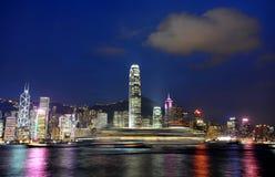 Hongkong night skyline. Hongkong island panorama and fast boat seen from Kowloon peninsula Royalty Free Stock Photos
