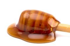 Honig auf Honey Spoon Spilled auf einem weißen Hintergrund stockbild