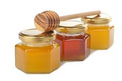 Honig in den Flaschen und im hölzernen Schöpflöffel stockbild