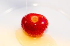 Honig, der auf Erdbeere gießt Stockbild