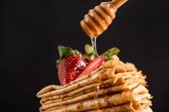 Honig, der auf Krepps oder Blini gießt stockfotos