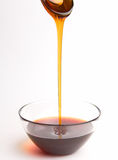 Honig, der aus dem Löffel gießt stockbilder