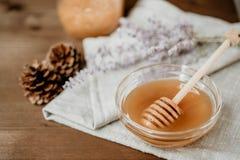 Honig in der Glasschüssel mit hölzernem Löffel und russischem Salbei über Holz lizenzfreies stockfoto