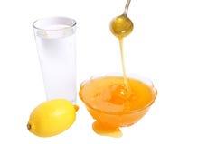 Honig in der Schüssel des Glases des Wassers und der Zitrone Lizenzfreies Stockfoto