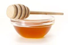 Honig in der Schüssel mit hölzernem Steuerknüppel Lizenzfreies Stockfoto