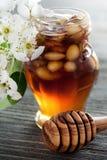 Honig in einem Glas mit Nüssen auf einem Holztisch Stockfotografie