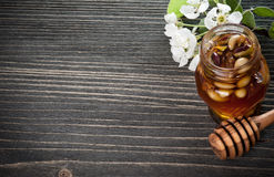 Honig in einem Glas mit Nüssen auf einem Holztisch Lizenzfreie Stockfotografie