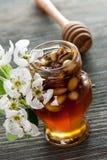 Honig in einem Glas mit Nüssen auf einem Holztisch Lizenzfreies Stockbild