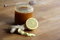 Honig, geschnittener Ingwer und halbe Zitrone stockfotos