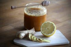 Honig, geschnittener Ingwer und halbe Zitrone stockbild