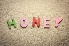 Honig geschrieben mit bunten hölzernen Buchstaben auf hellen Hintergrund Stockfoto