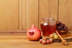 Honig, Granatapfel und Trauben über hölzernem Hintergrund Jüdisches neues Jahr Rosh-hashana Lizenzfreies Stockbild