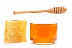 Honig im Glas mit Schöpflöffel und in der Bienenwabe auf lokalisiertem Hintergrund Stockbilder