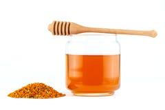 Honig im Glas mit Schöpflöffel und im Blütenstaub auf lokalisiertem Hintergrund Stockbilder