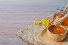 Honig im hölzernen Honigschöpflöffel lizenzfreie stockfotos