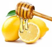 Honig mit dem hölzernen Stock, der auf eine Scheibe der Zitrone schüttet Stockfotografie