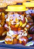Honig mit Nüssen in den Gläsern, die auf einander an einem angemessenen Markt stehen lizenzfreies stockfoto