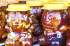 Honig mit Nüssen in den Gläsern, die auf einander an einem angemessenen Markt stehen stockbild