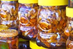 Honig mit Nüssen in den Gläsern, die auf einander an einem angemessenen Markt stehen lizenzfreie stockfotografie