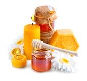Honig, natürliches Wachs und Wachskerzen über Weiß Lizenzfreies Stockfoto