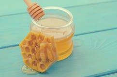 Honig und Honigzus?tze f?r seinen Gebrauch auf einem blauen h?lzernen Hintergrund stockfotografie