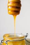 Honigbratenfett von einem hölzernen Honigschöpflöffel auf weißem Hintergrund Stockfotografie