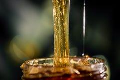 Honigbratenfett von einem Honigschöpflöffel   auf schwarzem Hintergrund Stockfoto