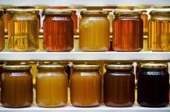 Honiggläser auf einem Regal Stockbild