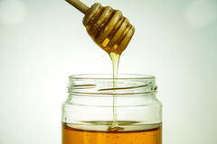 Honigglas mit Schöpflöffel Stockfoto