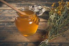 Honigglas und -nieselregen auf Holztisch Stockfotos