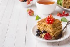 Honigkuchen mit Erdbeeren, Minze und Korinthe, eine Tasse Tee auf einem hellen Hintergrund lizenzfreie stockfotos