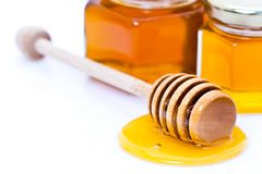 Honigschöpflöffel mit Honig stockbilder