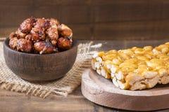 Honigstangen mit Erdnüssen - Holztisch lizenzfreies stockbild