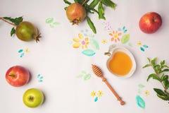 Honing, appelen en granaatappel op document achtergrond met waterverfbloemen Joods de vieringsconcept van vakantierosh Hashanah Stock Fotografie