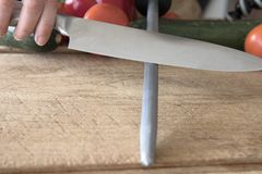 Honing Chef`s Knife. Knife on honing steel at 20 degree angle stock photo
