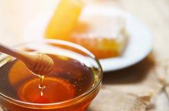 Honing die van de houten dipper achtergrond van de de honingraatplak van de honingskruik gele zoete druipen royalty-vrije stock afbeeldingen