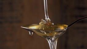 Honing die van de roestvrije theelepel druipen op houten achtergrond stock video