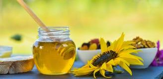 Honing die van een honingslepel in een glaskom druipen stock afbeeldingen