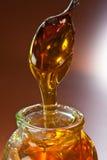Honing en een lepel stock afbeeldingen