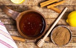 Honing en kaneel op een houten lijst stock fotografie